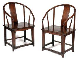 A pair of Chinese hardwood horseshoe-shaped armchairs, 18th century