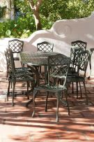 A green-painted wrought iron patio table and twelve chairs