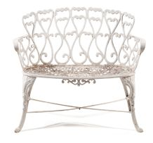 A white-painted cast-iron garden seat
