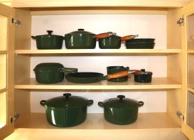 A group of Le Creuset green enamelled cast iron pots, modern