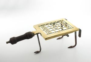 A brass and iron trivet, 19th century